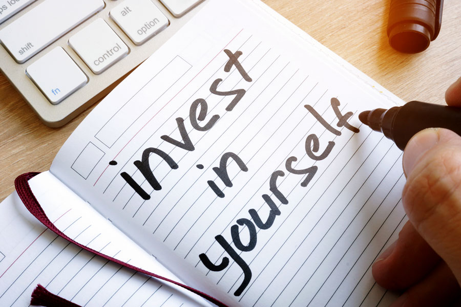 """invest in yourself written on notepad"""